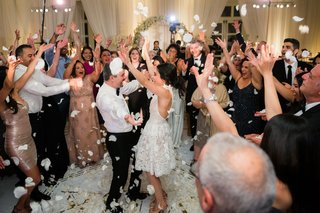 bride-in-second-wedding-dress-dancing-with-groom-without-jacket-at-reception-white-flower-petals