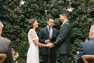 bride-in-short-sleeve-givenchy-wedding-dress-groom-with-officiant-in-front-of-hedge-wall-outdoor