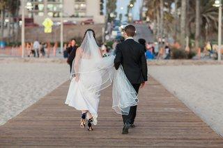 bride-carries-wedding-dress-train-groom-carries-cathedral-veil-bride-and-groom-walking-on-pier