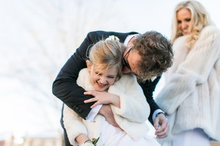 groom-hugs-new-stepdaughter-as-bride-watches-on-blended-family-wedding-winter-wedding-fur-coats
