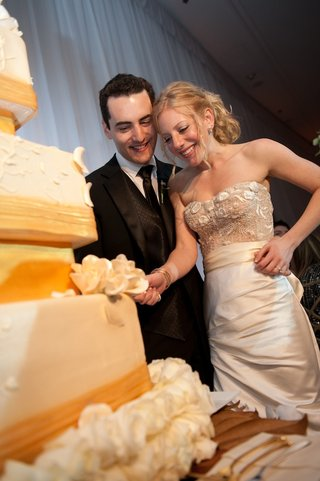 bride-and-groom-cut-into-wedding-cake-at-reception