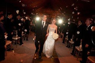 bride-and-groom-walk-between-strands-of-flowers
