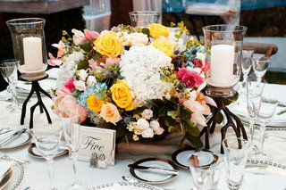 low-centerpiece-with-yellow-rose-blue-hydrangea-white-flowers-pink-flowers-thistle-unique-candles