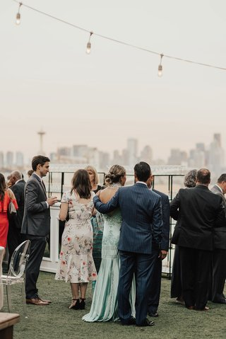 wedding-cocktail-hour-guests-enjoying-mingling-string-bistro-lights-seattle-skyline-water
