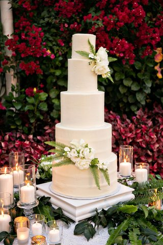 wedding-cake-in-front-of-bougainvillea-bush-white-ivory-round-layers-fresh-greenery-flowers-candles