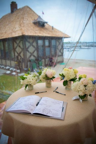 a-couples-guestbook-sitting-in-the-window-of-couples-reception-space-overlooking-a-harbor