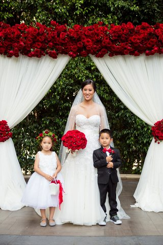 bride-in-liancarlo-flower-girl-with-red-rose-flower-crown-ring-bearer-in-red-bow-tie