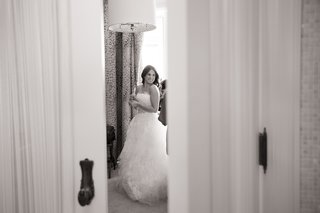 black-and-white-photo-of-bride-preparing-for-her-wedding-and-wearing-her-dress