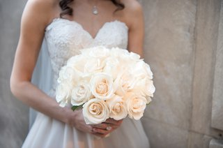 bride-in-essence-of-australia-wedding-dress-holds-bridal-bouquet-of-ivory-roses