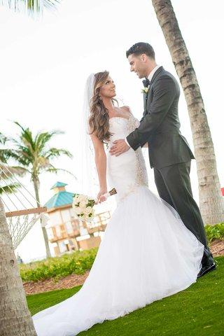 bride-in-mermaid-wedding-dress-maggie-sottero-with-hair-down-curls-groom-in-suit-acqualina-resort