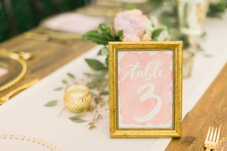 gold-frame-on-watercolor-table-number-with-blush-background