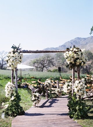 rustic-tree-trunk-arch-over-wood-plank-ceremony-aisle