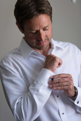 groom-getting-ready-for-wedding-day-in-white-button-up-down-shirt-with-black-cufflinks