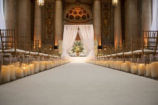 wedding-ceremony-white-aisle-runner-candles-along-side-hurricane-white-chuppah-flower-wall