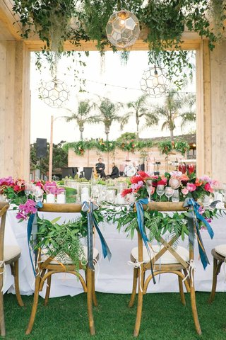 wedding-reception-bride-groom-chairs-decorated-with-ribbon-and-greenery-pink-centerpieces-tropical
