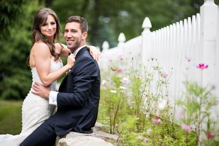 wedding-portrait-bride-in-strapless-wedding-dress-with-groom-in-suit-white-picket-fence-and-greenery