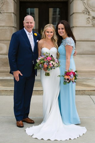 bride-in-strapless-lihi-hod-bridal-gown-in-between-mom-in-sky-blue-dress-and-dad-in-navy-suit