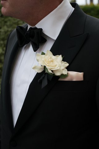 ivory-gardenia-boutonniere-on-groom-lapel-pocket-square-bow-tie-tuxedo