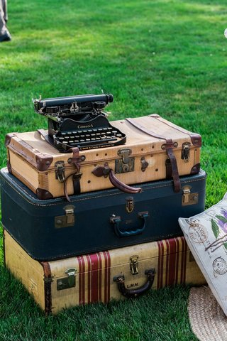 a-stack-of-vintage-luggage-cases-and-an-old-black-typewriter-resting-on-top-as-decor-cocktail-hour