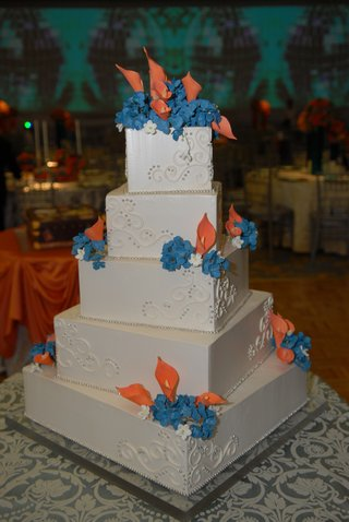 white-wedding-cake-with-orange-and-blue-sugar-flowers