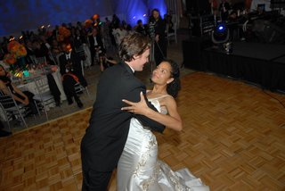 bride-in-a-reem-acra-gown-dances-with-groom-in-a-black-tuxedo