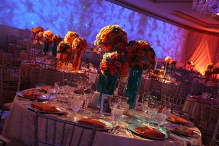 wedding-reception-table-with-three-centerpieces-of-colorful-flowers