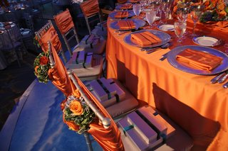 wedding-reception-head-table-with-orange-tablecloth-napkins-and-flowers