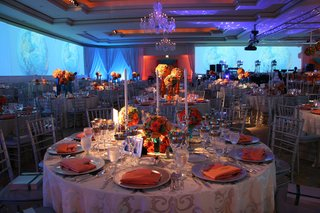 wedding-reception-table-with-candlesticks-and-orange-and-blue-flowers