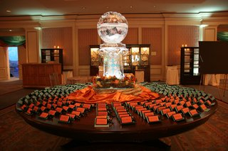 wedding-reception-place-card-table-with-globe-ice-sculpture-and-orange-and-teal-place-cards