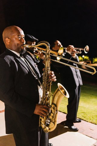 men-playing-saxophone-trombone-and-trumpet-at-wedding-reception-outside