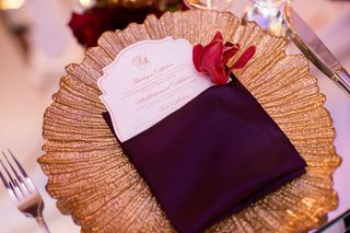 gold-texture-charger-plate-on-mirror-table-with-die-cut-wedding-dinner-menu-inside-purple-napkin