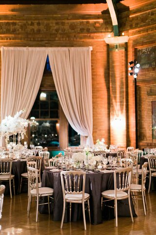 round-tables-with-silver-chairs-purple-linens-white-centerpiece-flowers-brick-drapery