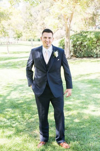 groom-posing-navy-suit-pink-tie-white-boutonniere-outside-smiling-before-catholic-ceremony