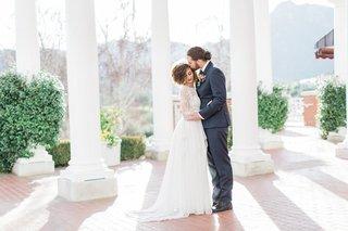 bride-in-long-sleeve-wedding-dress-and-groom-in-man-bun-at-sherwood-country-club