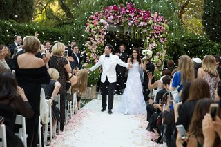 bride-and-groom-walking-up-aisle-as-husband-and-wife-flower-petal-cannon-going-off-white-petals