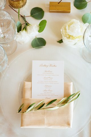 place-setting-with-neutral-hued-napkin-olive-sprig-menu