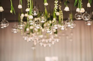 small-white-flowers-hanging-from-ceiling-with-suspended-glass-orbs-holding-tiny-candles