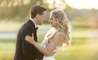 blonde-bride-with-hair-half-up-smiles-with-groom-groom-grips-bride-on-the-waist