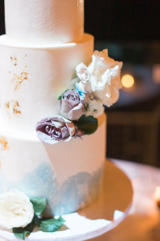 close-up-of-wedding-cake-with-gold-foil-and-light-blue-water-color-details-and-fresh-flowers