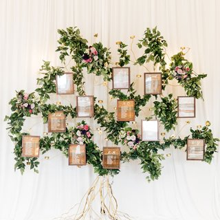 wedding-reception-seating-chart-wood-grain-alphabetical-on-gold-structure-with-greenery-purple-bloom