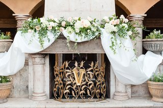 custom-gold-cover-with-initial-monogram-white-drapery-and-blush-ivory-flowers-greenery-on-mantel