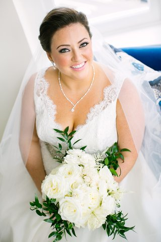 bride-in-v-neck-wedding-dress-lace-pretty-necklace-earrings-white-bouquet-eyeliner-pink-lipstick