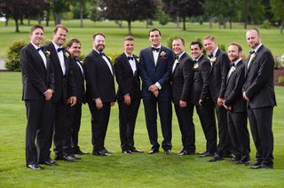 groomsmen-in-black-suits-with-navy-bow-ties-and-groom-in-navy-suit-with-black-bow-tie