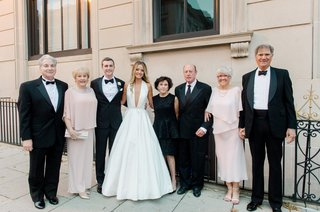 bride-in-romona-keveza-a-line-gown-plunging-neckline-with-groom-and-families