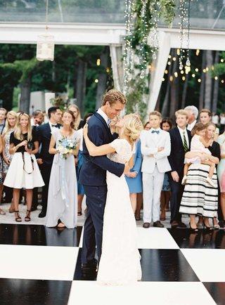 bride-in-carolina-herrera-short-sleeve-lace-wedding-dress-with-groom-in-navy-tuxedo-on-dance-floor