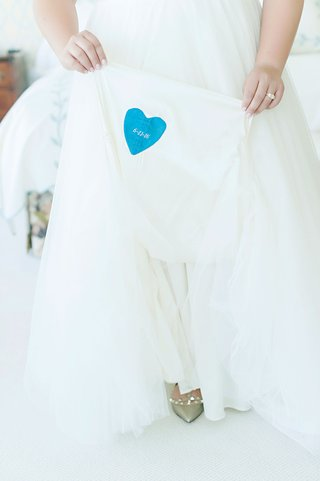 bride-holding-up-wedding-dress-something-blue-heart-sewed-into-gown-wedding-date