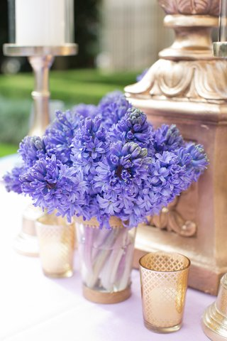wedding-reception-table-with-bright-purple-hyacinths-in-a-clear-vase-with-gold-rims