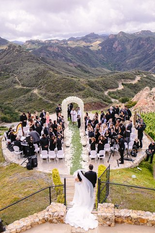 malibu-rocky-oaks-ceremony-white-chairs-ivory-floral-arch-bride-in-riki-dalal-couture