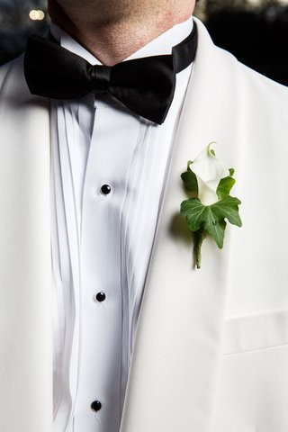 wedding-on-new-years-eve-ideas-groom-in-tuxedo-white-jacket-black-bow-tie-calla-lily-boutonniere