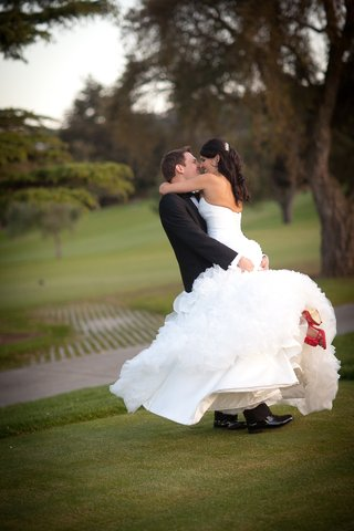 groom-in-black-tuxedo-hugs-bride-in-a-maggie-sottero-dress-with-ruffled-skirt